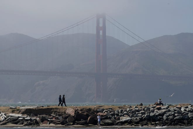 People walk on a path in front of the Golden Gate Bridge in San Francisco, Sunday, April 26, 2020, during the coronavirus outbreak. (AP Photo/Jeff Chiu)