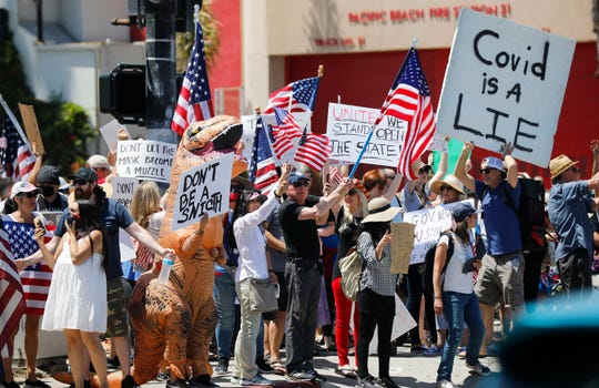 Protesters stand along Mission Blvd. during A Day of Liberty rally in Pacific Beach in San Diego, Sunday, April 26, 2020. The protesters were rallying against the government shutdown due to the coronavirus outbreak. (K.C. Alfred/The San Diego Union-Tribune via AP)