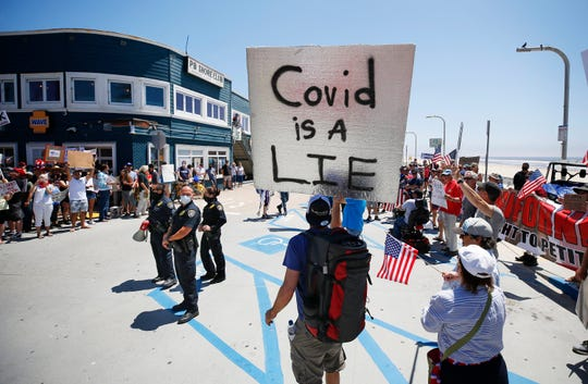 Protesters stand along Mission Blvd. during A Day of Liberty rally as police officers look on in Pacific Beach in San Diego, Sunday, April 26, 2020. The protesters were rallying against the government shutdown due to the coronavirus outbreak. (K.C. Alfred/The San Diego Union-Tribune via AP)