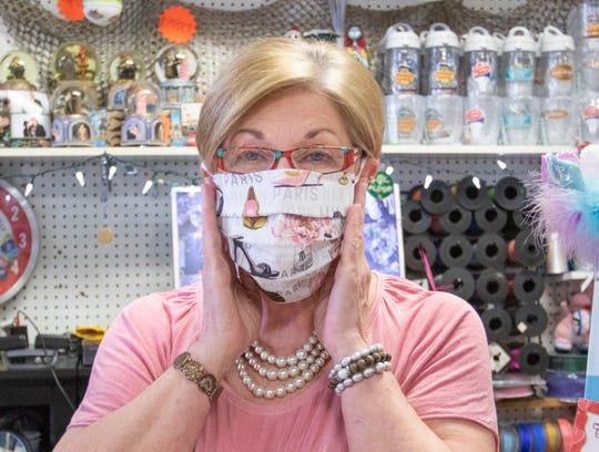 Owner Carol Campbell models one of the face masks made by her sister that are for sale at the Blue Sky Gift Shop in Gulf Breeze on Monday, April 27, 2020.