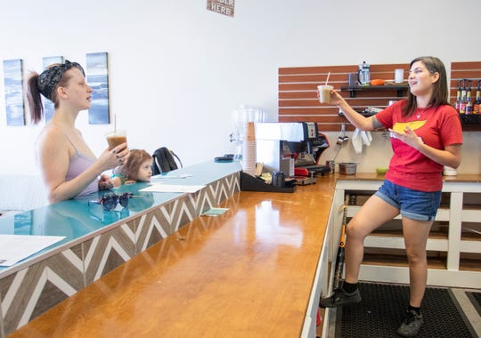"""Co-owner Keri Clark, right, offers a traditional Fijian """"Bula"""" toast to Laura Catherine Morgan at Pacific Kava on North Ninth Avenue in Pensacola on Monday, April 27, 2020. Bula, which means life, is used like the Hawaiian word aloha as a greeting and to wish good health."""