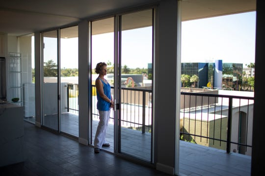 Real estate agent Mary Jordan looks out a space available to move into at Regency Towers in Phoenix on April 24, 2020.