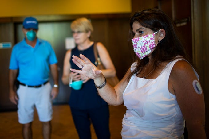 Real estate agent Christa Lawcock (right) shows off a space to perspective clients at Regency Towers in Phoenix on April 24, 2020. Lawcock had started the tour of the apartment wearing a mask due to precautions for the COVID-19 pandemic.