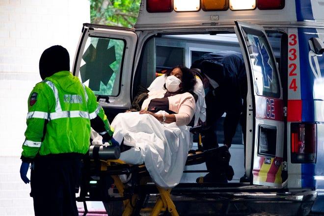 Los técnicos médicos de emergencia transportan a un paciente desde una ambulancia al llegar a la bahía de emergencia en el Hospital de la Universidad George Washington en Washington, DC, EE. UU., 27 de abril de 2020.