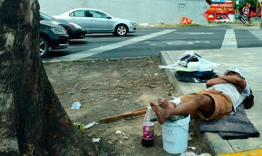 Un hombre que trabaja en la calle descansa este lunes en un andén de Ciudad de México.