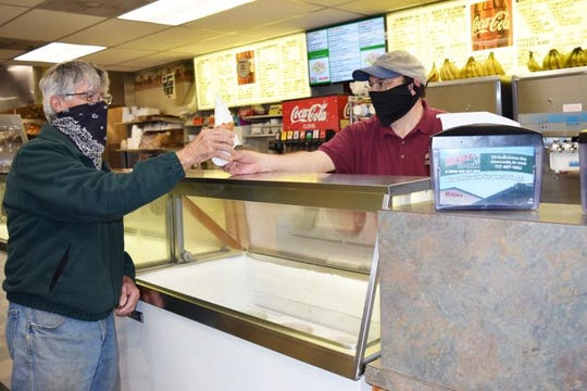 Mikie's Ice Cream owner Marty Boscolo serves a cone to Dave Friese as the Greencastle restaurant continues selling carryout food continues under COVID-19 regulations.
