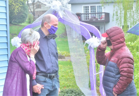 """With the special date advanced, Layne made do with a combination of two previously purchased wedding garb options that weren't in her original plans. She also crafted a unique """"bow-tie mask"""" for her new husband, Bob, to wear while greeting guests."""
