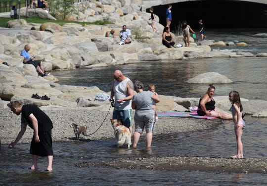 People enjoy the warmer weather at the Truckee River in downtown Reno on Monday April 27, 2020.