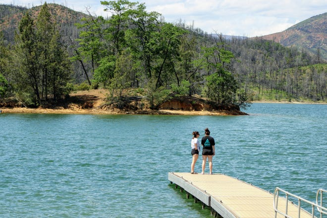 Two women stand on a dock overlooking Whiskeytown Lake near the Brandy Creek boat ramp on Friday, April 24, 2020.