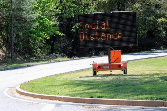 A sign at the entrance of Whiskeytown National Recreation Area tells visitors to social distance due to coronavirus concerns on Friday, April 24, 2020.