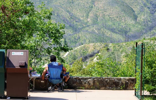 A man sits in a folding chair overlooking Whiskeytown National Recreation Area in the visitor center parking lot on Friday, April 24, 2020.