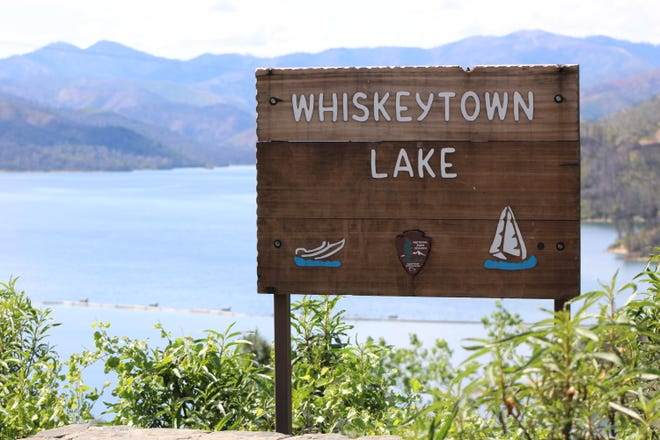 A sign stands in front of Whiskeytown Lake next to the visitor center just off Highway 299 in Shasta County on Friday, April 24, 2020.