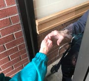 Karel Birdsall reaches out to her husband during a visit Wednesday, April 22, 2020, through the glass of the nursing home where Bill Birdsall lives in Mt. Angel.
