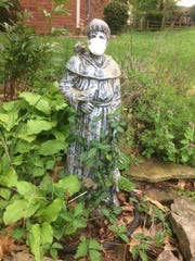 A statue of St. Francis wears a medical mask, symbolizing protecting oneself and others from COVID-19