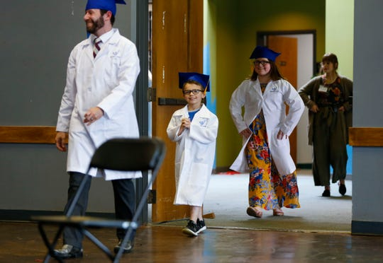 Rob Blevins, Discovery Center executive director, leads in Sylus and Lillian Barnett for a live streamed graduation ceremony on Monday, April 27, 2020. The Discovery Center responded to the COVID-19 pandemic by offering its 60,000-square-foot space to families of health care workers and first responders as a licensed emergency child care facility.