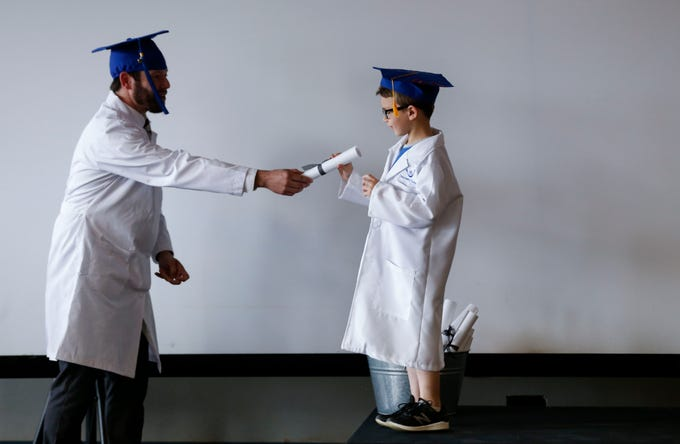 Rob Blevins, Discovery Center executive director, hands a diploma to Sylus Barnett during a live streamed graduation ceremony on Monday, April 27, 2020. The Discovery Center responded to the COVID-19 pandemic by offering its 60,000-square-foot space to families of health care workers and first responders as a licensed emergency child care facility.