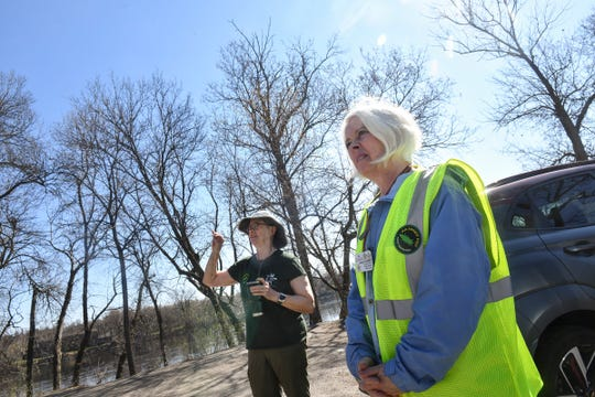 Volunteers Maureen Graber, left, and Linda G. Tenneson talk about the methods they use to identify trees damaged by emerald ash borer Monday, April 27, 2020, along the Mississippi River near St. Cloud.