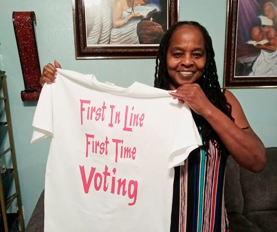 In this photo taken by her son, Betty Riddle in Sarasota, Fla., Sunday, April 26, 2020, holds the T-shirt she wore on March 17, 2020, when she voted for the first time. She was barred from voting in Florida until a federal judge temporarily blocked the state from preventing her and 16 other felons from voting because of unpaid legal financial obligations.
