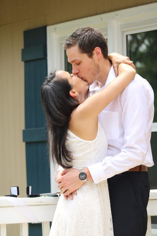 Jason Khan-Hohensee kisses Yasmin Khan-Hohensee at the wedding at their home on April 18.