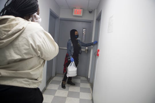 """Charly """"Evol"""" Bass, left, and Elosha Anderson deliver hot meals to elderly in need Sunday, April 26, 2020, in Wilmington."""