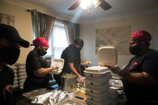 Joy Watson, from left, Aliyah Bass, Tracey Williams, and Nema Bass prepare hot meals to be delivered to local seniors in need during the pandemic Sunday, April 26, 2020.