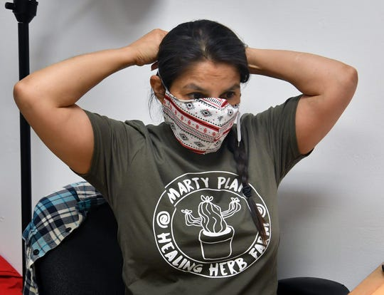 Ruthie Turnbo demonstrates one of the cloth face masks she sews for people to wear to comply with CDC guidelines if they are out in public.