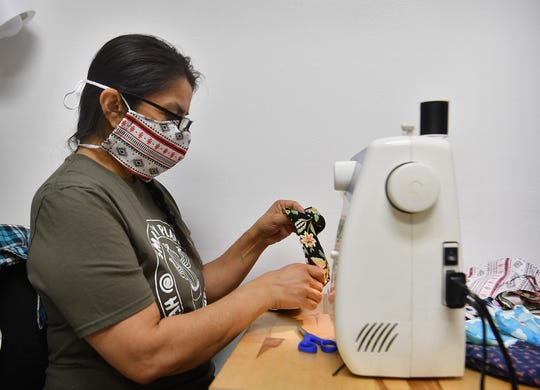 Ruthie Turnbo uses a sewing machine in the back of her Smarty Plants business in the Hamilton Building to make cloth face masks to help stop the spread of the coronavirus.