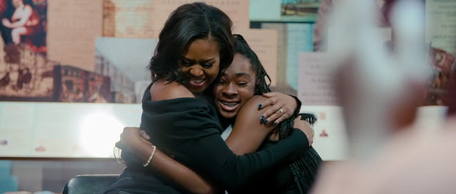 """Michelle Obama (left) hugs a young fan at a Philadelphia community event in a scene from the Netflix documentary """"Becoming."""""""