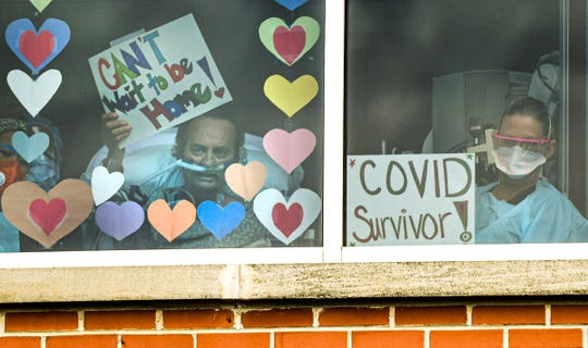 """Richard Frady, left, of Hartwell, Georgia, a recovering COVID-19 patient in the Intensive Care Unit at AnMed Health in Anderson, waves a """"Can't Wait to be Home!"""" sign on his 32nd day after diagnosis, to his wife Sally Frady and daughter Allison Nissen of Atlanta, from his window at the hospital with medical staff in  Anderson, S.C. Tuesday, April 28, 2020."""