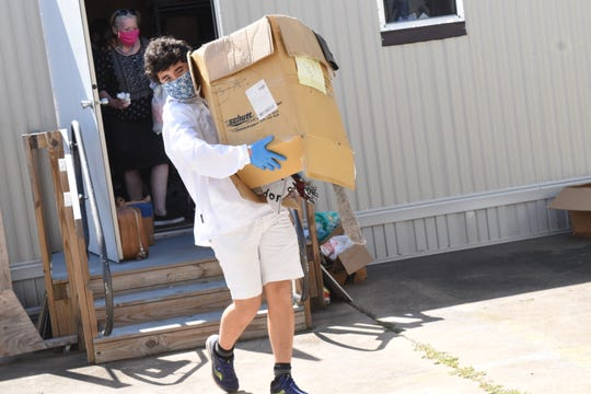 Jake Noda, a 15-year-old student at Holy Savior Menard High School, helps clean out a shed at the Central Louisiana Homeless Coalition's  Virginia Soprano Housing Resource Center on Jackson Street.