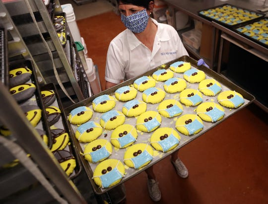FILE — Stephanie Sluys places a finished tray of happy face cookies wearing masks into the rack after she and Angelica Pinera created their icing faces at Sluys Poulsbo Bakery on Tuesday, April 28, 2020. The bakery's popular happy and sad face cookies now come with a masked option in response to COVID-19.