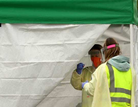 FILE — Danielle Kincaid, LPN, (left) and Dezerae Hamblin, CNA, collect a swab from a walk-up patient in a tent at the Peninsula Community Health COVID-19 testing site at the Kitsap County Fairgrounds on April 28.  Inset image on wide displays