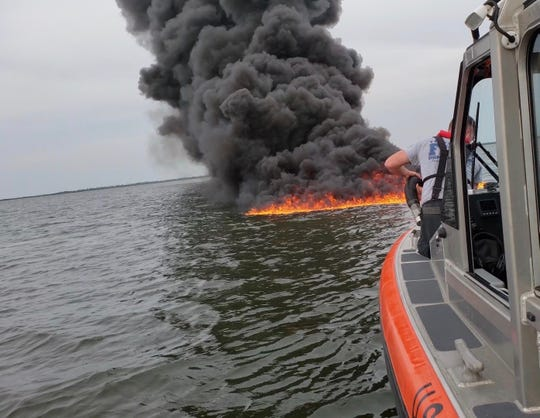 A U.S. Coast Guard vessel approaches a burning boat that sank Sunday afternoon in the Indian River Lagoon near Titusville.