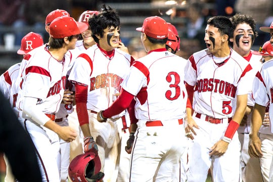 Robstown High School's Ryan Garza celebrates with teammates after hitting a two-run inside-the-park home run in 2015. The Pickers clinched their 27th district championship.