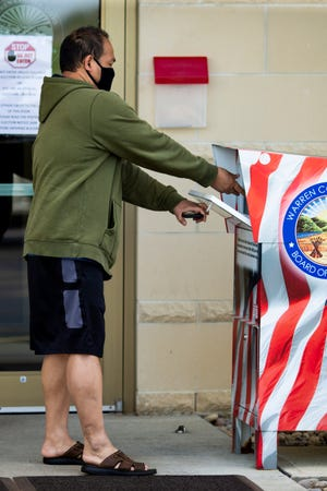 A voter turns in his ballot to the dropbox in front of Warren County Board of Elections in Lebanon, Ohio on Tuesday, April 28, 2020.