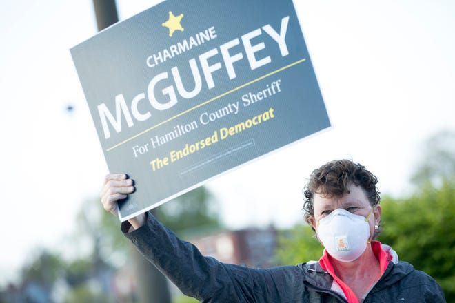 Charmaine McGuffey holds a sign while campaigning for Hamilton County Sheriff outside the Hamilton County Board of Elections on Tuesday, April 28, 2020, in Norwood.