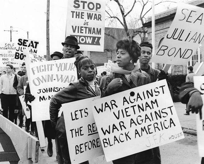 """A protest against the war in Vietnam marches down South Water Street in Kent across from the old courthouse on February 12, 1966. The """"Seat Julian Bond"""" sign refers to the Georgia State Legislature's refusal to seat newly elected member Julian Bond because of his affiliation with the Student Nonviolent Coordinating Committee, one of the major American Civil Rights Movement organizations of the 1960s. The SNCC opposed the war in Vietnam."""