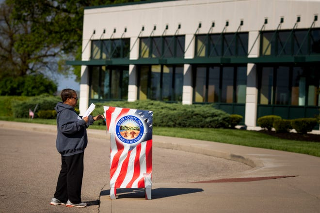 A voter turns in her ballot to the dropbox in front of Butler County Board of Elections in Hamilton, Ohio on Tuesday, April 28, 2020.