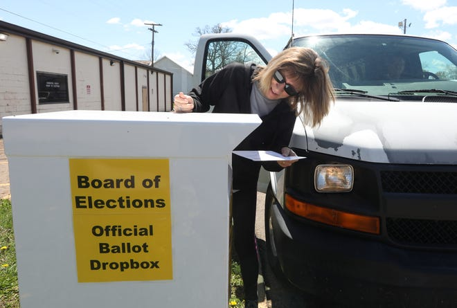 Cindy Massie puts her ballot in the drop box outside the Coshocton County Board of Elections on Monday.