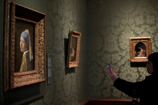 """A visitor takes a picture of Johannes Vermeer's 17th century masterpiece """"Girl with a Pearl Earring,"""" left, at Mauritshuis in The Hague, Netherlands on June 20, 2014."""