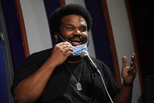 """In this April 20, 2020, photo, comedian Craig Robinson lowers his mask as he performs during a """"Laughter is Healing"""" stand-up comedy livestream event at the Laugh Factory comedy club in Los Angeles. With comedy clubs closed and concert tours put on hold, comics like Robinson, Tiffany Haddish, Will C  and others are keeping the jokes flowing on webcasts and Zoom calls even without the promise of a payday, because they say the laughs are needed now more than ever."""
