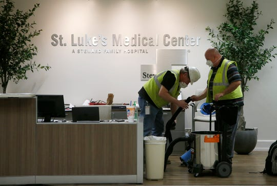 Contract workers join the Army Corps of Engineers as they get the currently dormant St. Luke's Hospital ready for reopening for the possible surge of coronavirus patients in Phoenix.