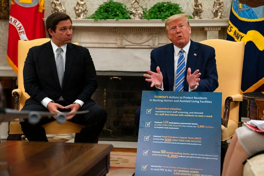 Gov. Ron DeSantis, R-Fla., listens as President Donald Trump talks about the coronavirus response during a meeting in the Oval Office of the White House, Tuesday, April 28, 2020, in Washington.