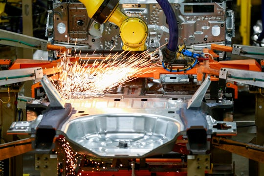 FILE - In this June 24, 2019, file photo machines work on a Ford vehicle assembly line at Ford's Chicago Assembly Plant in Chicago. Ford, General Motors and FCA factories have been idled for over a month due to fears of spreading the coronavirus. (AP Photo/Amr Alfiky, File)