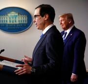 President Donald Trump listens as Treasury Secretary Steven Mnuchin speaks about the coronavirus in the Press Briefing Room of the White House, Tuesday, April 21, 2020, in Washington.