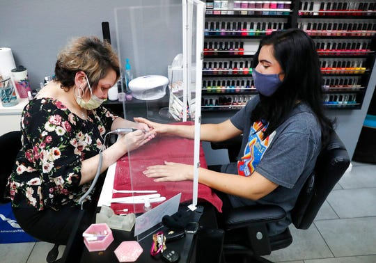In this April 24, 2020, file photo, manicurist Rhonda Simpson, left, polishes nails for her customer Faith at the reopened Salon A la Mode in Dallas. The salon installed a barrier between the two to avoid the spread of COVID-19.