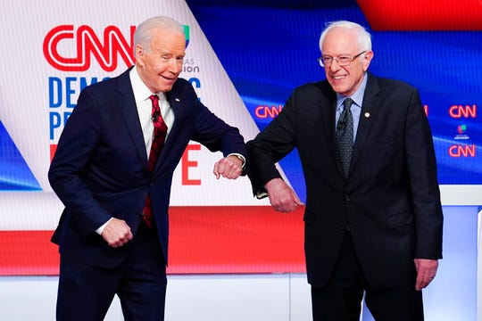 Former Vice President Joe Biden, left, and Sen. Bernie Sanders, I-Vt., right, greet each other before they participate in a Democratic presidential primary debate at CNN Studios in Washington in this March 15, 2020, file photo.