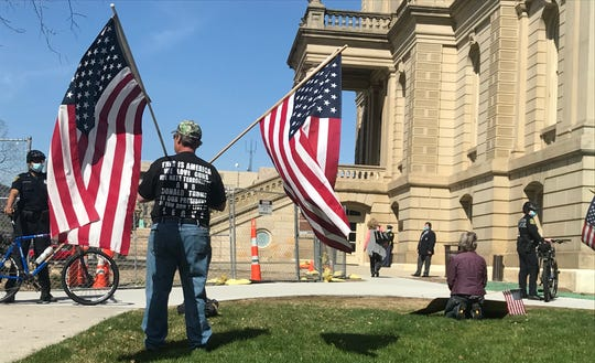 A group of about 30 protesters wait outside the Michigan Capitol after the Senate adjourned on Tuesday, April 28, 2020. The protesters were demonstrating against restrictions aimed to stem the spread of COVID-19.