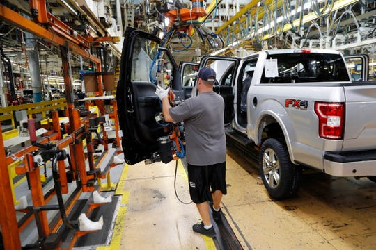 FILE- In this Sept. 27, 2018, file photo a United Auto Workers assemblyman installs the front doors on a 2018 Ford F-150 truck being assembled at the Ford Rouge assembly plant in Dearborn.