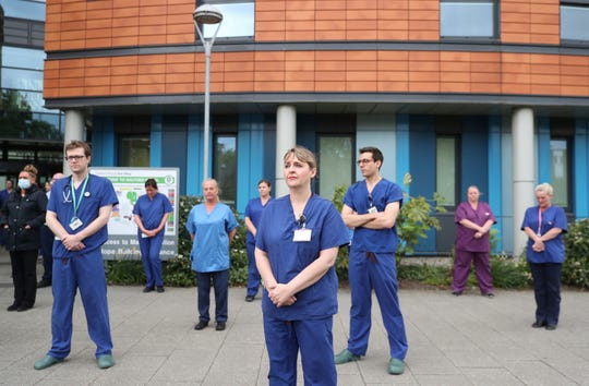 Staff stand outside Salford Royal Hospital in Manchester, England, Tuesday April 28, 2020, during a minute's silence to pay tribute to the NHS staff and key workers who have died during the coronavirus outbreak.